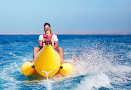 Photo pour happy family, delighted father and son having fun, riding on banana boat during summer vacation - image libre de droit