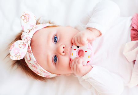 Photo pour cute little baby girl nibble a silicone doughnut teether - image libre de droit