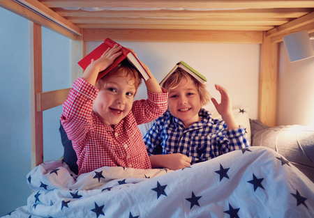 Foto de cheerful kids, brothers having fun, playing with books on the bunk bed during bedtime - Imagen libre de derechos