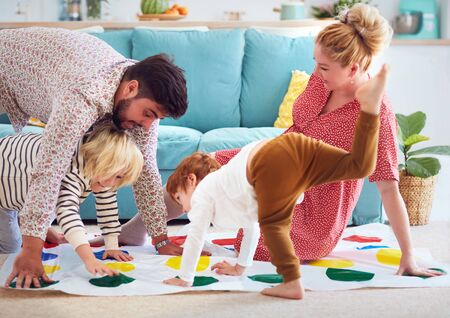 Foto de happy family having fun together, playing twister game at home - Imagen libre de derechos