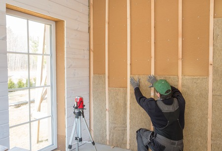 Foto de Construction worker thermally insulating eco-wood frame house with wood fiber plates and heat-isolating natural hemp material. Finishing the walls with a white wooden board, using laser line level. - Imagen libre de derechos