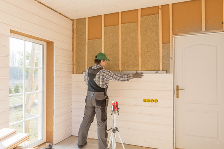 Foto de The worker makes finishing works of walls with a white wooden board, using laser line level. Building heat-insulating eco-wooden frame house with wood fiber plates - Imagen libre de derechos