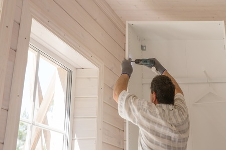 Photo pour The process of assembling furniture, the master assembles a white cabinet using an electric drill in a room with a white wooden finish - image libre de droit