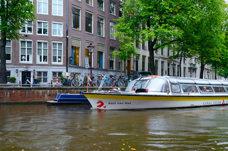 Foto de AMSTERDAM, NETHERLANDS - SEPTEMBER 6, 2018: Unidentified tourists are on sightseeing pleasure boat on canal in historic center of city, Amsterdam, North Holland, Netherlands - Imagen libre de derechos