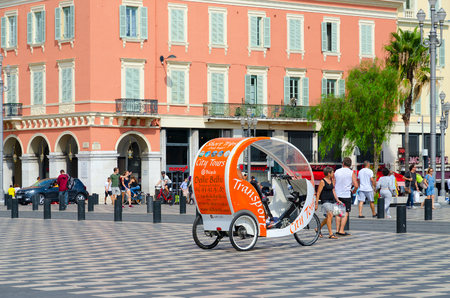 Foto de NICE, FRANCE - SEPTEMBER 15, 2018: Walking excursion bike car on Place Massena. Promenade du Paillon. Unknown people walk down street - Imagen libre de derechos
