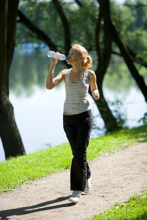 Young woman V Running drinking water isolated on white