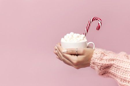 Photo pour Female hands in knitted sweater holding cup of marshmallows and Christmas candy cane on pink background Flat Lay copy space Winter traditional food Festive decor celebration presents Xmas holiday. - image libre de droit