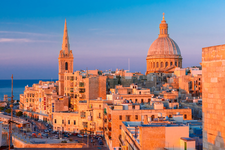Foto de View from above of the domes of churches and roofs at beautiful sunset with churches of Our Lady of Mount Carmel and St. Pauls Anglican Pro-Cathedral, Valletta, Capital city of Malta - Imagen libre de derechos