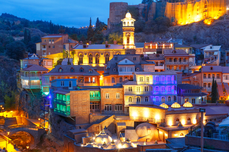 Foto de Amazing View of Jumah Mosque, Sulphur Baths and famous colorful balconies in old historic district Abanotubani in night Illumination during morning blue hour, Tbilisi, Georgia. - Imagen libre de derechos