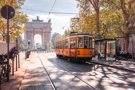 Foto de Famous vintage tram in the centre of the Old Town of Milan in the sunny day, Lombardia, Italy. Arch of Peace, or Arco della Pace on the background. - Imagen libre de derechos