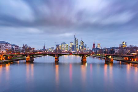 Foto de Picturesque view of Frankfurt am Main skyline and Ignatz Bubis Brucke bridge during evening blue hour with mirror reflections in the river, Germany - Imagen libre de derechos