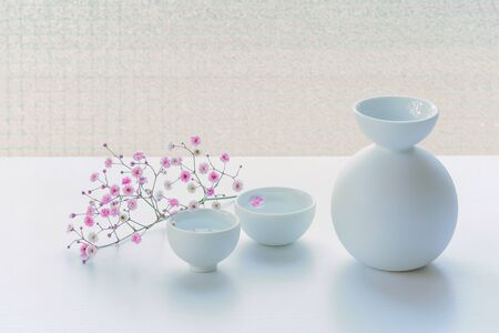 Photo for Bottle of Japanese style on a white table, decorated with pink small flowers. - Royalty Free Image