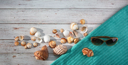 Photo for Top view. Variety of shells, beach towel, starfish, sunglasses, goggles placed on light wooden bachground. Seaside vacation, snorkeling, diving. Family holidays. - Royalty Free Image