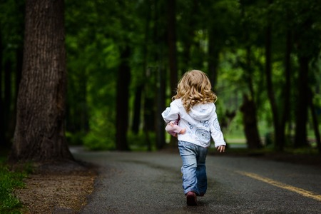 Photo pour Little blonde girl walks away to dark park alone - image libre de droit