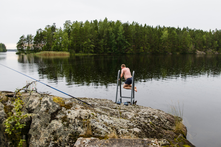 Photo pour Man jumping to lake water after taking finnish sauna - image libre de droit