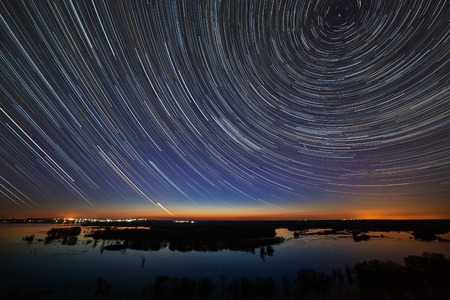 Foto de Star trails in the night sky. A view of the starry space in the background of the river. - Imagen libre de derechos
