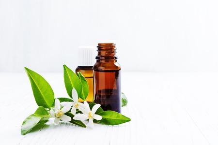 Photo pour Neroli (Citrus aurantium) essential oil in a brown glass bottle with fresh white  flowers on ligth background. Selective focus. - image libre de droit