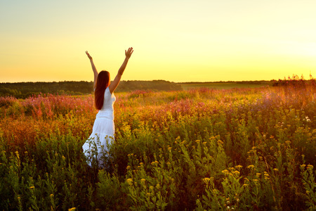 Young woman in white clothes standing in field on sunset