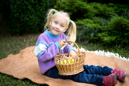 Foto de Funny little girl playing on nature on woolen blanket. Beautiful girlie holding yellow apple, relax in the garden. beauty of autumn park. Round shape of big apple. day picnic in the village, fresh air - Imagen libre de derechos