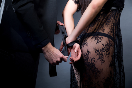 Foto de Lovers man and woman are preparing for role-playing games. Dominate obey undress seduce a partner. Girl dressed in black lacy negligee, wearing sexy underwear. A sensual date idea. Thematic bdsm party - Imagen libre de derechos
