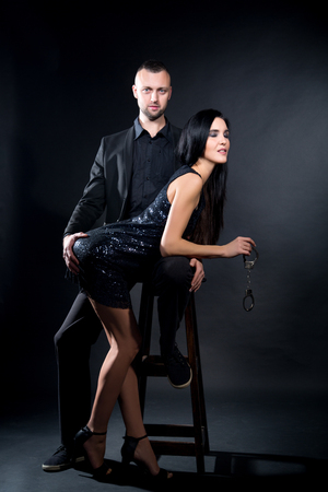 Photo for Lovers man and woman are preparing for role-playing games. Dominate obey undress seduce a partner. Girl dressed in black lacy negligee, wearing sexy underwear. A sensual date idea. Thematic bdsm party - Royalty Free Image