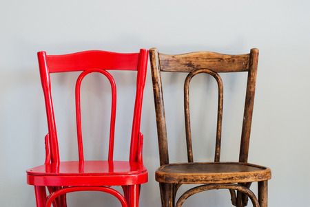 Photo for Pair of Red and Brown Chairs on a Grey Wall - Royalty Free Image