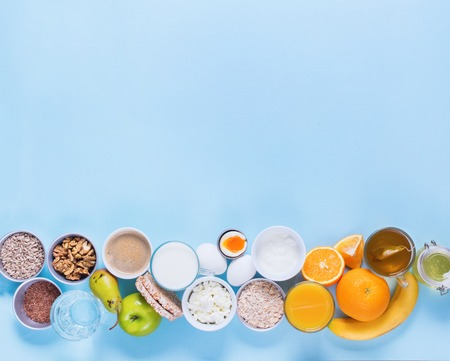 Foto de Useful Colorful Breakfast Coffee Milk Tea Fruits Cottage Cheese Oats Flat Lay Still Life Table Top View Blue Background - Imagen libre de derechos