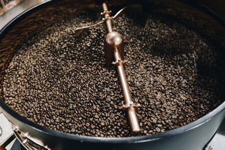 Foto de The freshly roasted coffee beans from a large old coffee roaster being stirred in the cooling cylinder. Fresh coffee beans. - Imagen libre de derechos