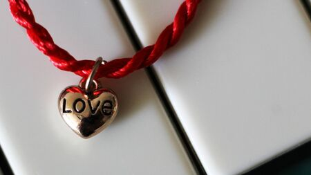 Photo for A heart of gold and a scarlet thread on piano, jewelry - Royalty Free Image