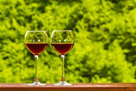 Foto de Two glasses of red wine on the deck of a wooden house on a green fresh forest background. Copyspace. - Imagen libre de derechos