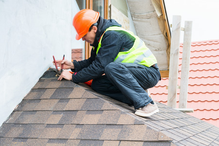 Photo pour Roofer builder worker dismantling roof shingles - image libre de droit