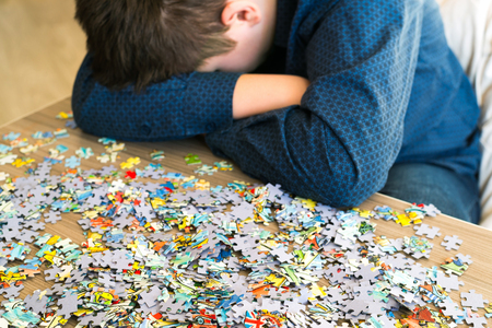 Photo for Tired teenager is sitting tilting his head next to the puzzles - Royalty Free Image