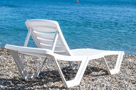 Foto de Empty white plastic chaise lounge on the background of the sea - Imagen libre de derechos