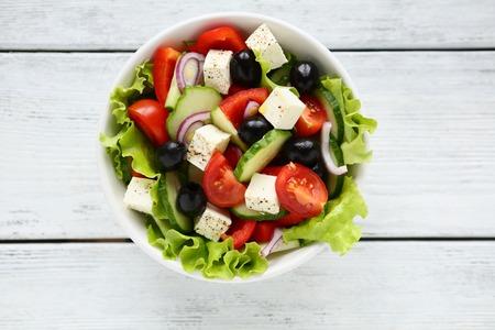 Foto de Fresh Greek salad in a bowl, top view - Imagen libre de derechos