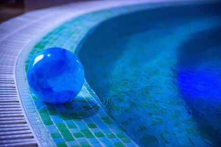 Photo pour Blue ball is left in swimming pool decorated with blue and green mosaic tiles. Stairs are visible through shallow water. Summer season and private safety on water concepts. Selective focus. Copy space - image libre de droit