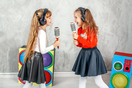 Foto de Funny kids singing and listening to music on headphones. The concept is childhood, lifestyle, dance, music. - Imagen libre de derechos