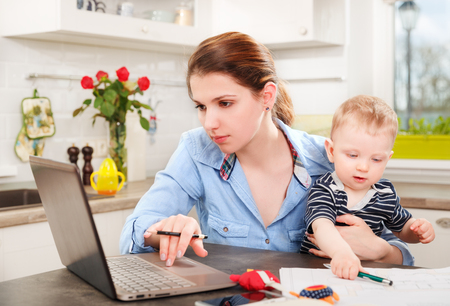 Photo for Young mother working with her baby at home - Royalty Free Image