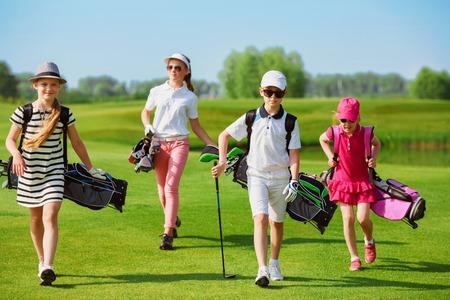 Foto de Kids walking on fairway with bags at golf school - Imagen libre de derechos