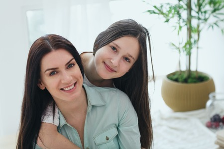 Photo for Beautiful mother and her cute daughter smiling and posing at home. - Royalty Free Image