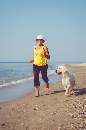 Photo pour Elderly woman running with her golder retriever - image libre de droit