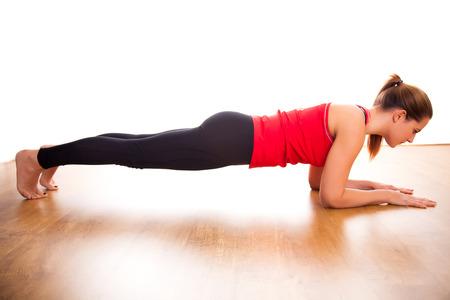 Foto de Young woman exercising - doing a plank in a studio - Imagen libre de derechos