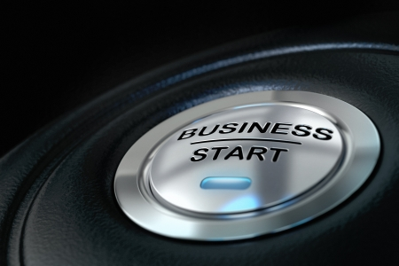 pushed business start button over black background, blue light, symbol of new businesses