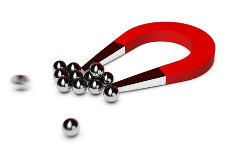 Foto de red horseshoe magnet attracting some chrome balls, white background - Imagen libre de derechos