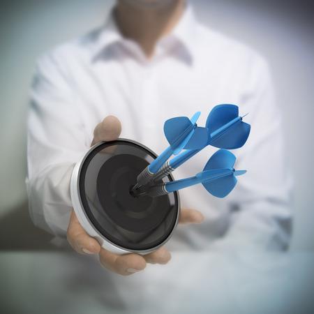 Foto de Man holding on black target with three blue darts hitting the center. - Imagen libre de derechos