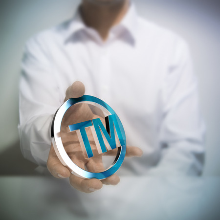 Foto de Man holding metallic trademark symbol. Concept image for illustration of intellectual property or protection of products or services. - Imagen libre de derechos