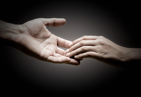 Photo pour two hands are touching each other over black background, concept of solidarity or empathy. - image libre de droit