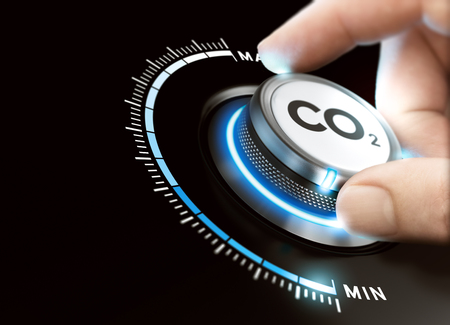 Foto de Man turning a carbon dioxyde knob to reduce emissions. CO2 reduction or removal concept. Composite image between a hand photography and a 3D background. - Imagen libre de derechos