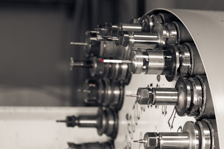 Foto per Rotating head with drilling machine bits and tools in a high precision mechanics plant at CNC lathe in workshop - Immagine Royalty Free