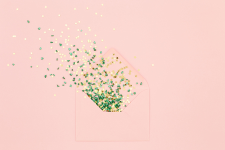 Foto de Festive Sequins explosion from envelope on pink background. Cheerful greeting card. Shiny Gold stars and pebbles. Congratulations on holidays. Minimal flat lay design - Imagen libre de derechos