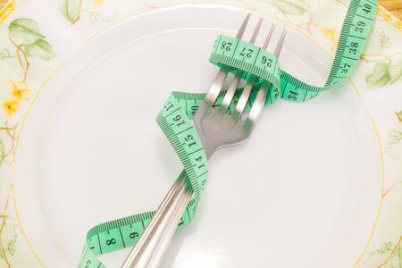 Foto de Empty plate with measure tape, knife and fork. Diet food on wooden table - Imagen libre de derechos
